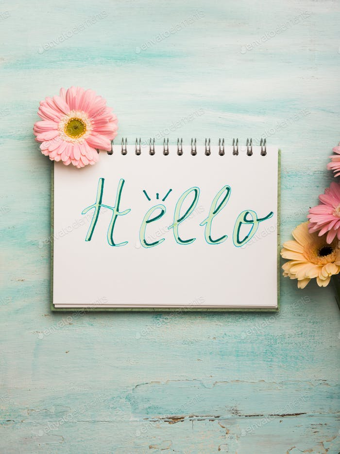 Hello word written on notebook page. Flowers