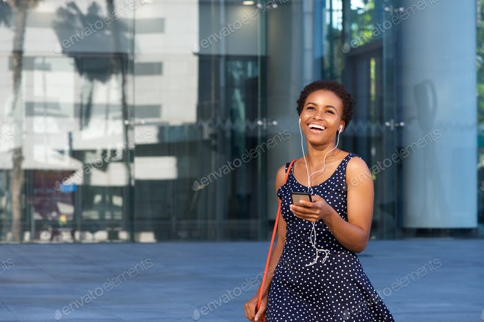young african woman walking in city with mobile phone and earphones