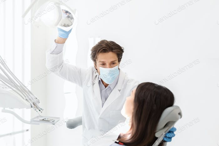 Attentive dentist listening to female patient in cabinet