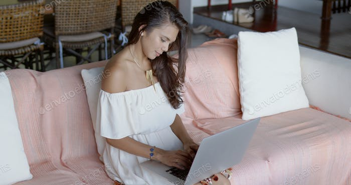 Young woman sitting on sofa and typing on laptop