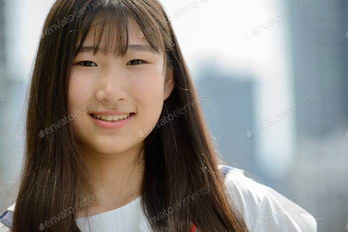 Happy young beautiful Asian teenage girl against view of the city
