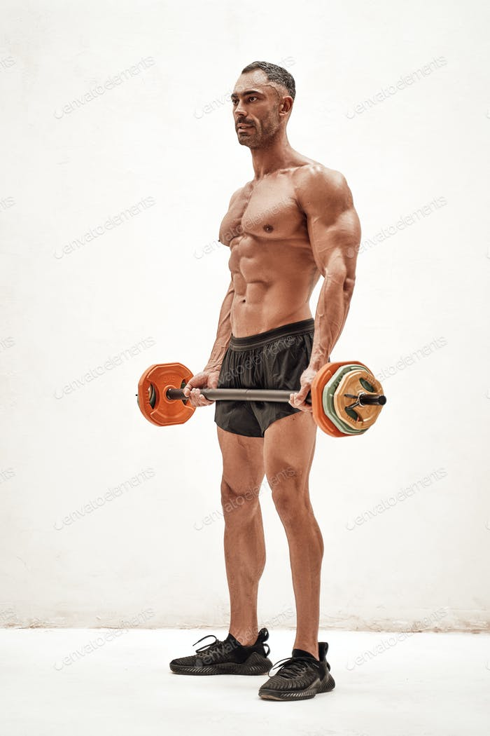 Shirtless adult male bodybuilder doing an exercise with a barbell in a bright studio