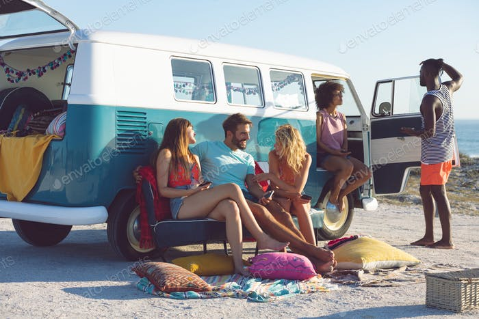 Front view of young group of diverse friends interacting with each other near camper van at beach