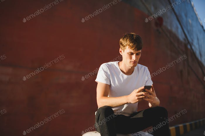 Portrait of boy with brown hair sitting with cellphone in hands and dreamily looking in it