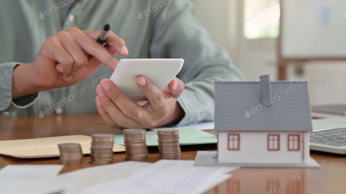Hand is using calculator to calculate the home expenses.