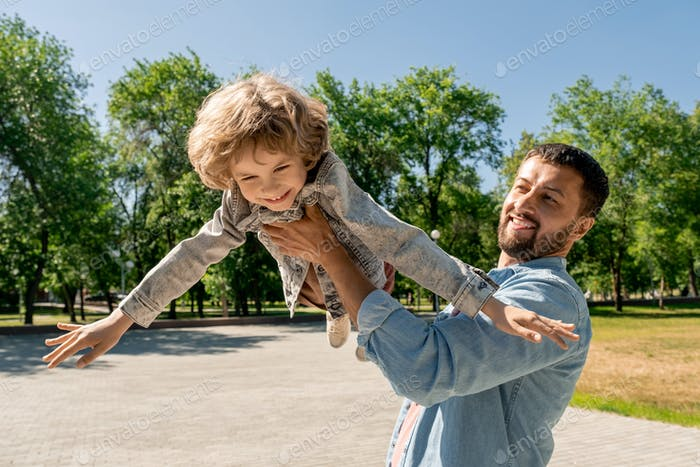 Happy young man holding his cute cheerful little son, lifting and whirling him