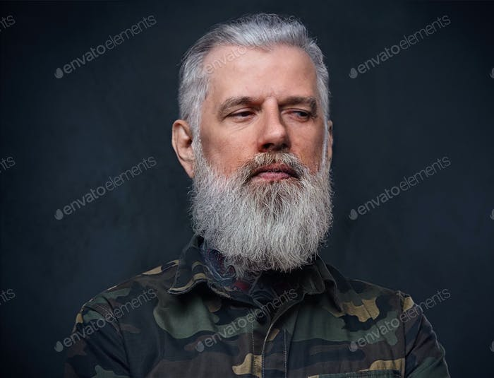 Martial grandfather in camouflage clothing poses in dark background