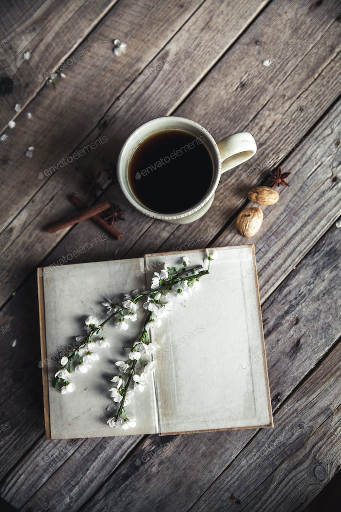 Large Cup of coffee on vintage wooden background. Spring flowers and books