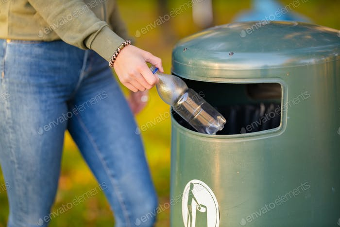 Midsection of woman putting bottle in garbage bin