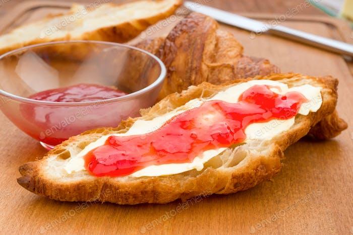 Croissant in Butter und Marmelade auf Holz bestrichen