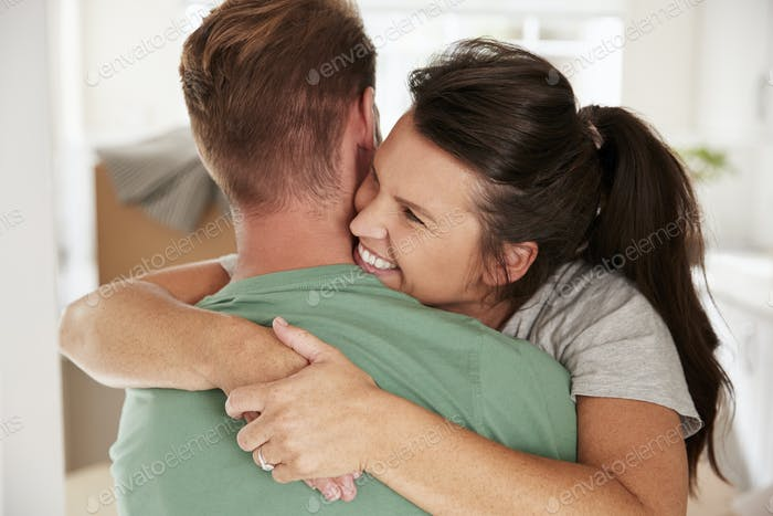 Loving Couple Celebrating With A Hug At Home