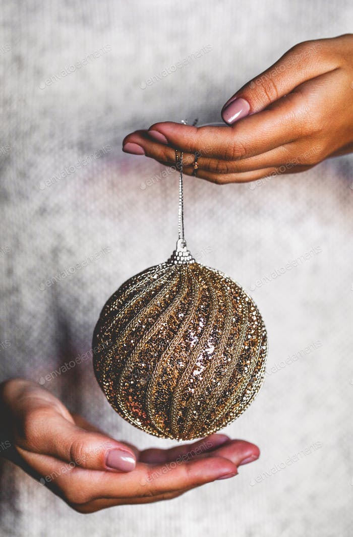 Woman in warm sweater holding toy glass decorative ball in hands, copy space. Christmas
