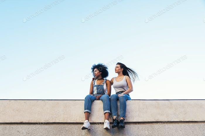 Beautiful women seating in the street.