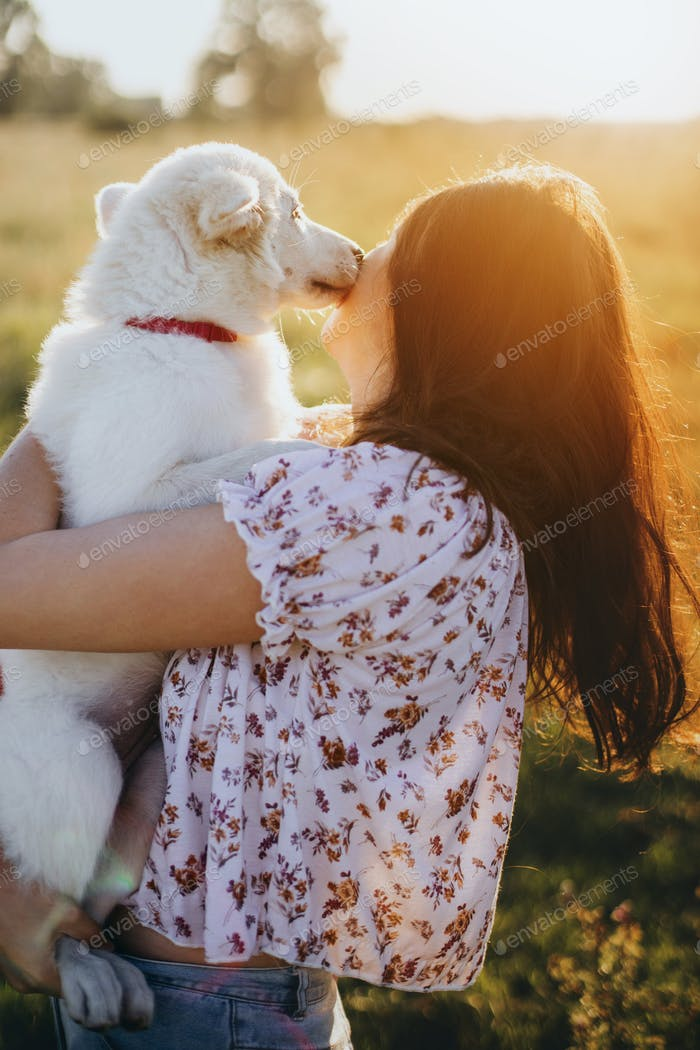 Adorable fluffy puppy kissing girl