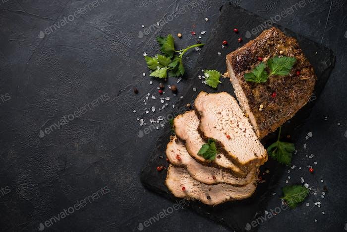 Baked pork meat ham on black kitchen table