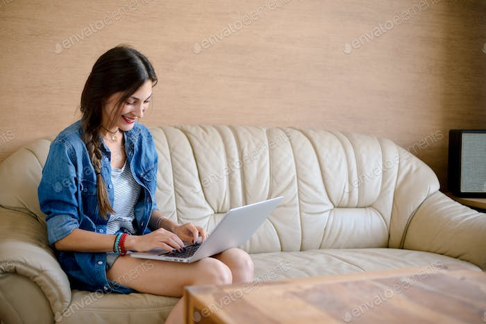 Attractive lady usig laptop on leather sofa