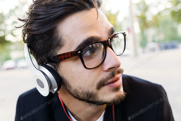 Handsome young man listening to music in the street.