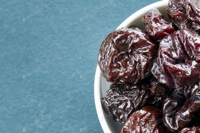 Dried plums in a bowl, shallow depth of field.