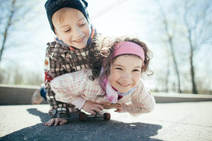 little boy and girl skaiting on the street