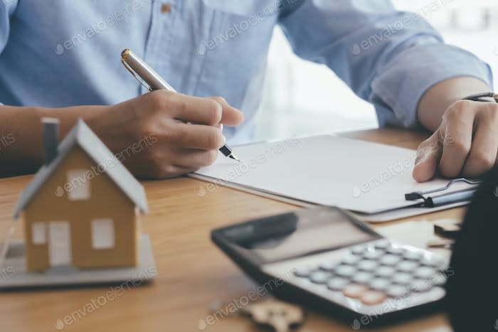 Young man is signing financial contract with real estate agent at selling office.