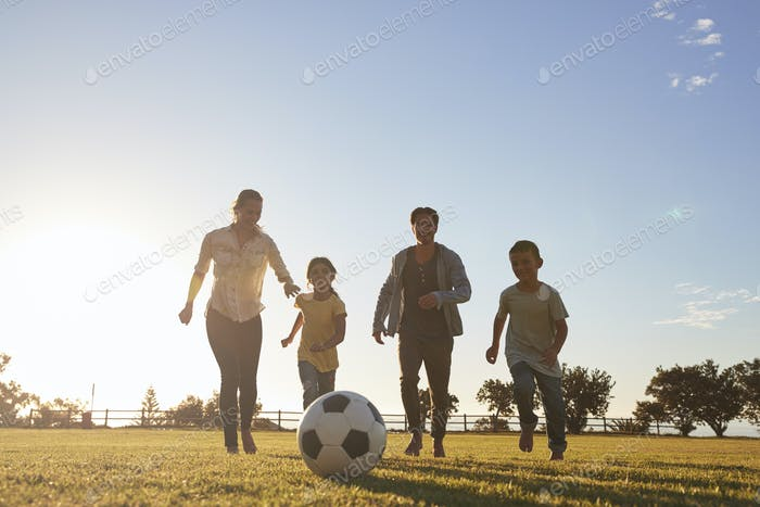 Young family running after a football in a park