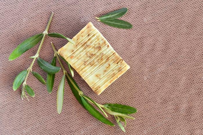 Handgemachte Seifenriegel und Olivenzweige auf gunny Hintergrund. Ansicht von oben