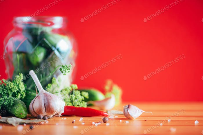 Ingredients, spices and herbs for canning cucumbers on red background. Copy space. Dill flowers, bay