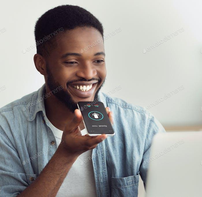 Schwarzer Kerl mit Smartphone-Sprachassistent Sitzen zu Hause