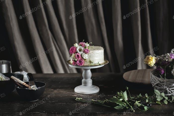 white cake with flowers on dark background