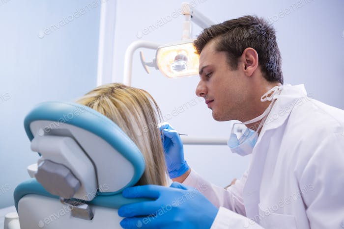 Side view of dentist polishing  woman teeth