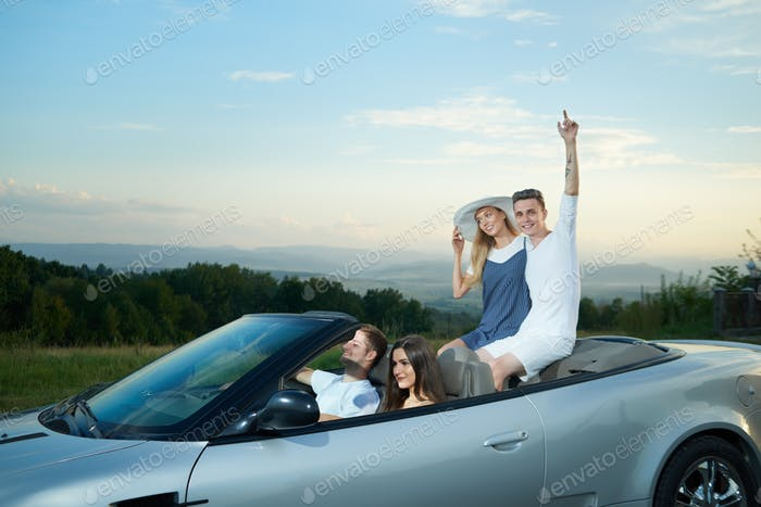 Two couples driving on luxurious silver cabriolet