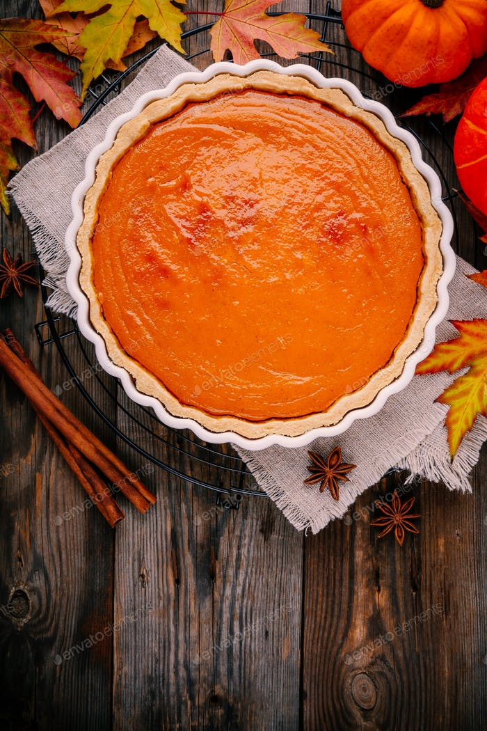 Homemade Pumpkin Pie for Thanksgiving with whipped cream and cinnamon on wooden background