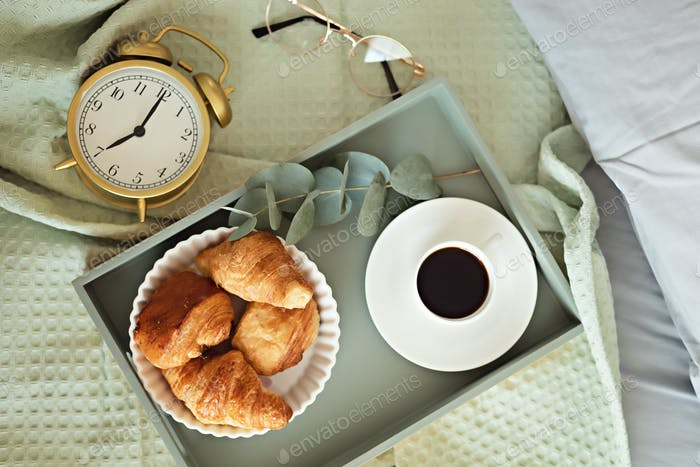 Alarm clock and coffee cup at bed in sunny room. Easy morning start, positive day beginning, waking