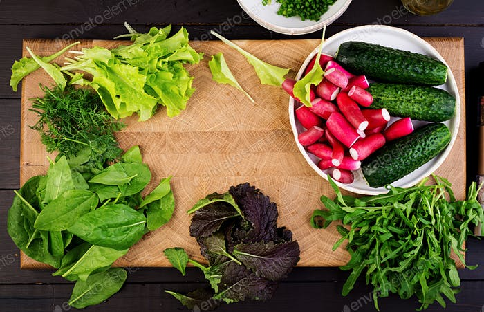 Ingredients for fresh salad of cucumbers, radishes and herbs. Flat lay. Top view