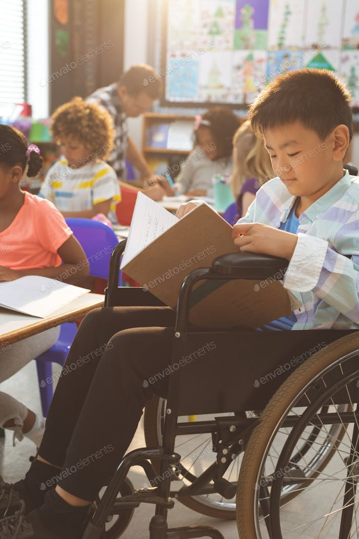 Side view of schoolboy studying in classroom while sitting at wheelchair in classroom at school