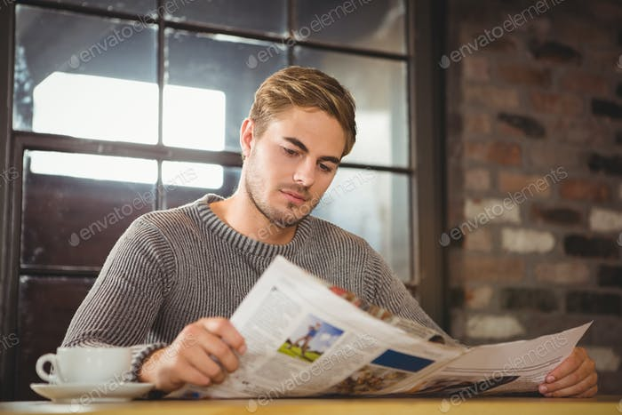 Handsome man having coffee and reading newspaper at coffee shop
