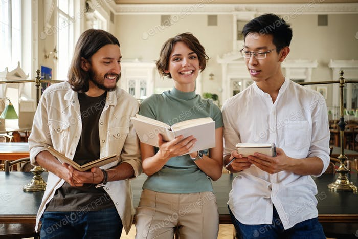 Group of young casual multinational students joyfully studying making notes in library of university