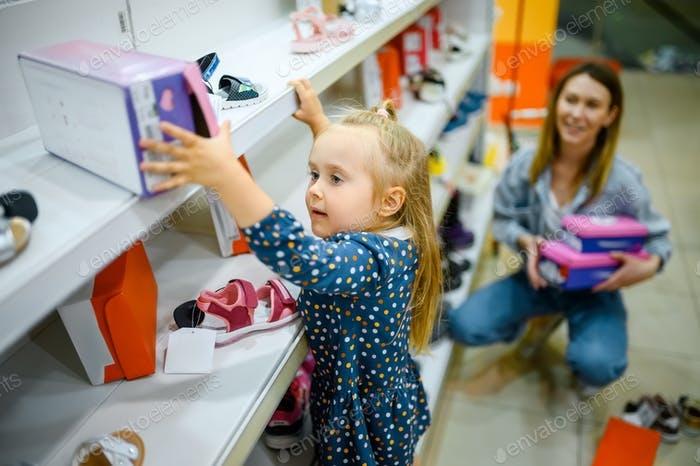 Little baby climbs on showcase to takes a shoes