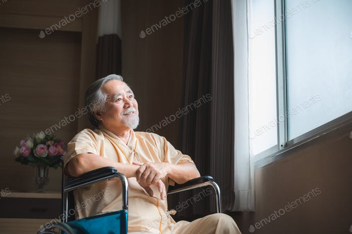 Eldery senior male patient sitting on wheel chair and looking outside of the hospital window