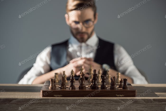 close-up view of chess board with pieces and young businessman behind