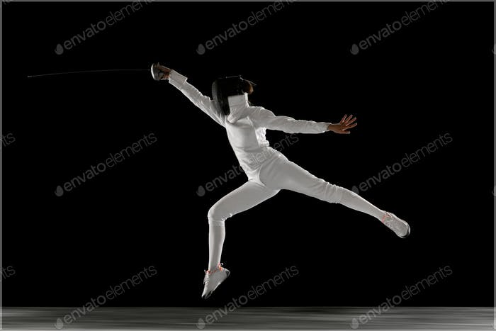 Teen girl in fencing costume with sword in hand isolated on black background