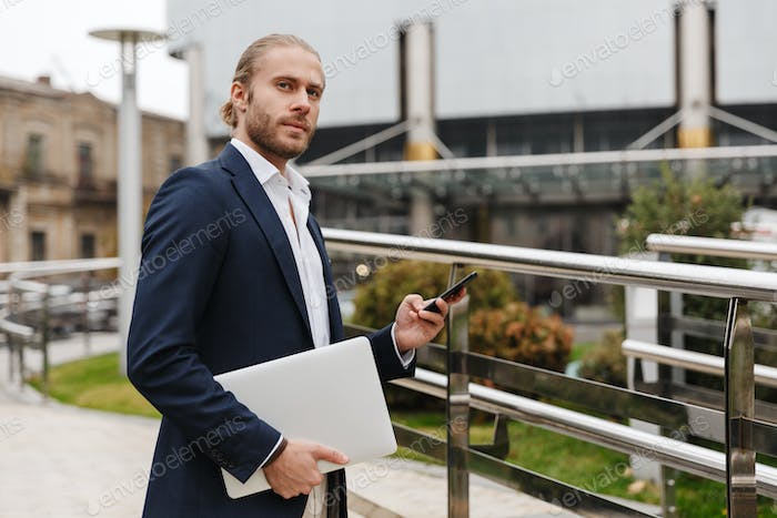 Handsome young bearded businessman standing outdoors