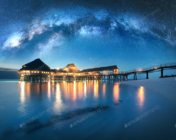 Milky Way and wooden bungalow on the water in summer starry night