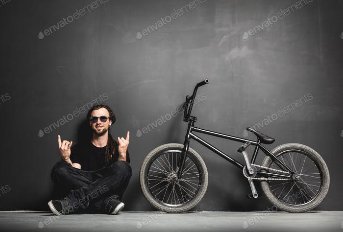 Happy man sitting next to his BMX bike, showing rocker gesture.