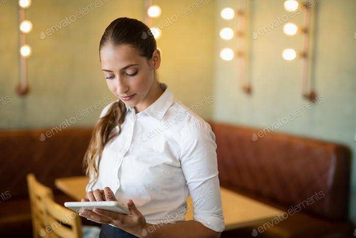 Waitress using digital tablet in bar
