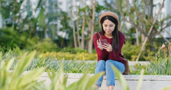 Mujer uso del teléfono móvil en la ciudad y sentarse en el banco en el parque