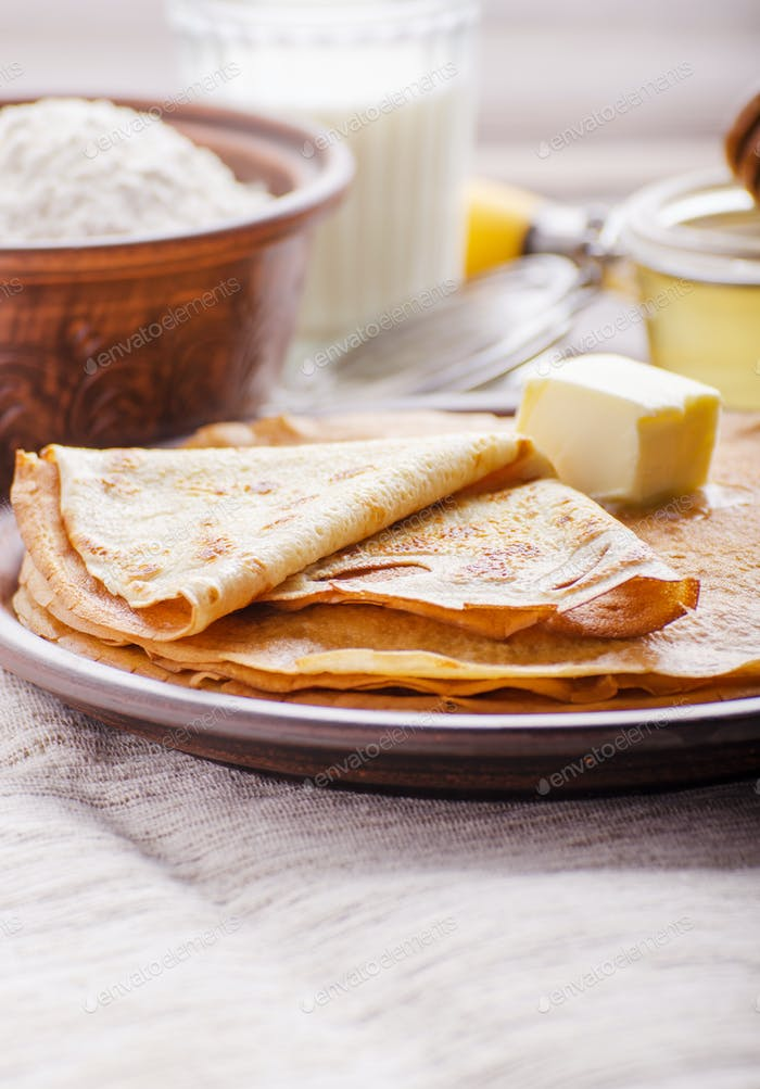 French crepes with butter flour milk and honey in ceramic dish o