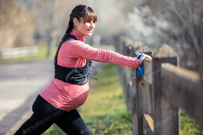 Pregnant young woman stretching after running in the park.