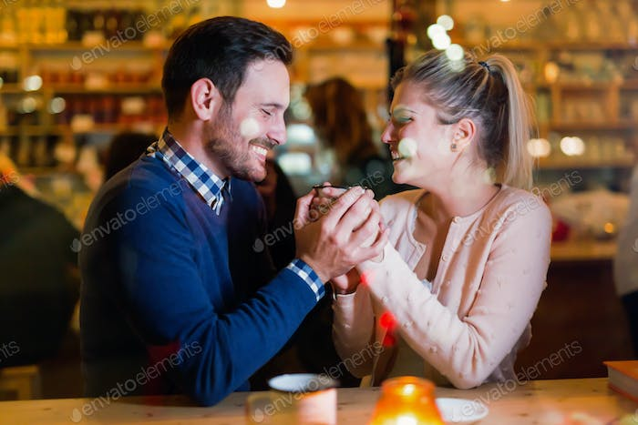 Happy couple talking at bar and having date