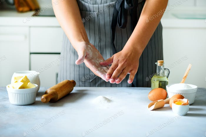 Female hands kneading dough, baking background. Cooking ingredients - eggs, flour, sugar, butter